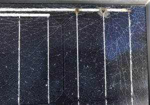 Picture of a solar panel with burned connections and the entire glass front is cracked.