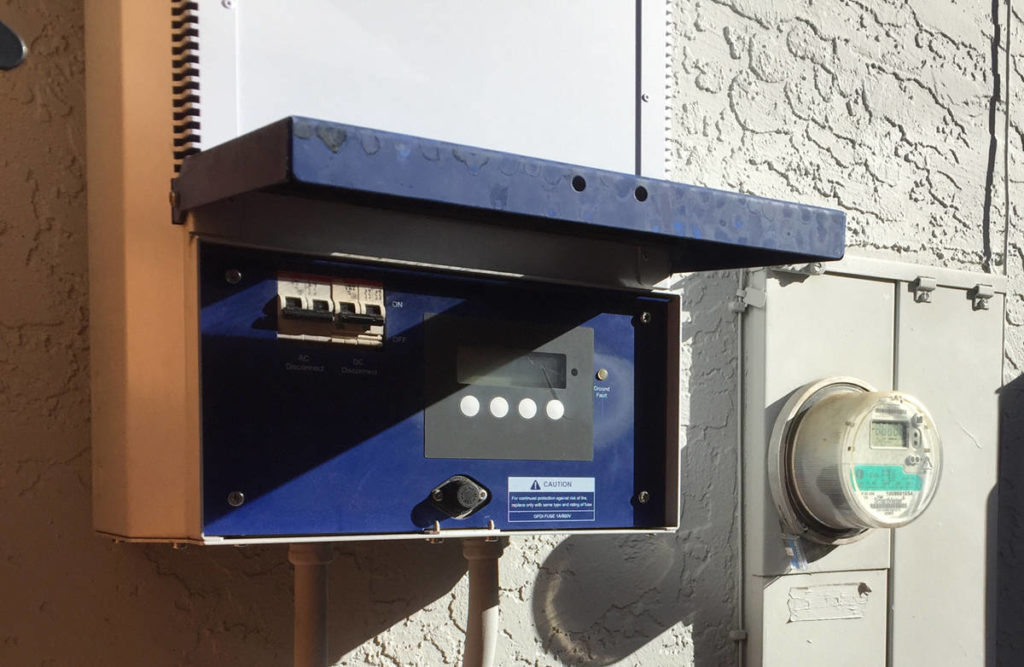 Photo of Fronius IG inverter with lower panel open and showing the AC and DC disconnects to the left of the display